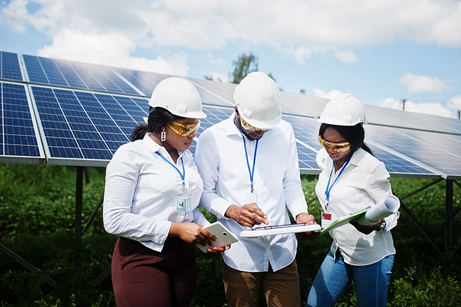 Three solar panel technicians review notes